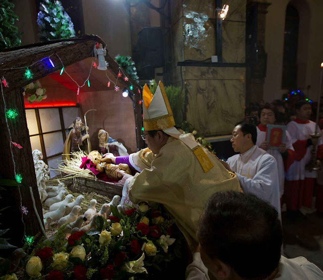 Chinese bishop Joseph Li Shan places a statue of baby Jesus in a replica of a stable as he takes part in a mass on the eve of Christmas at the South Cathedral official Catholic church in Beijing, China, Wednesday, Dec. 24, 2014. (AP Photo/Ng Han Guan)